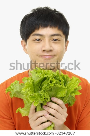 Close up young man holding fresh bunch salad - stock photo