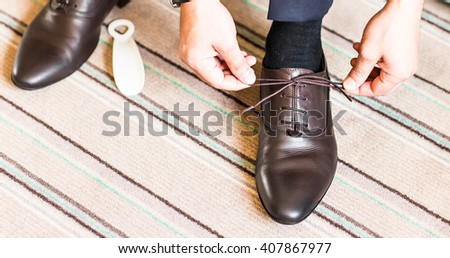 Close-up young man tying elegant shoes indoors