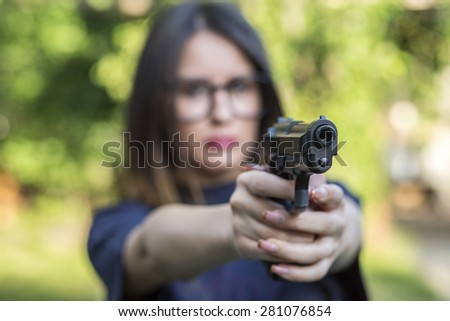 Close up Young Pretty Woman Pointing a Gun at the Camera with both Hands - stock photo