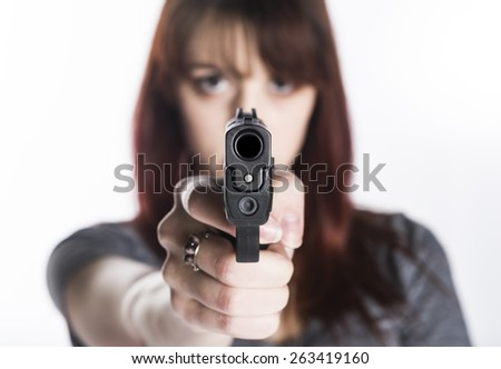 Close up Young Pretty Woman Pointing a Gun at the Camera with One Hand, Isolated on White Camera. - stock photo