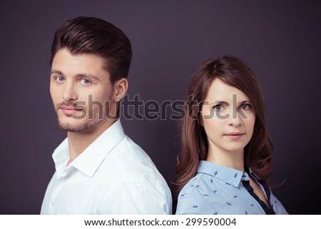 Close up Young Professional Couple in Back to Back Staring at the Camera Against Dark Gray Wall Background. - stock photo