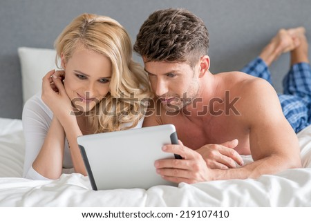 Close up Young Sweet Couple on Bed Watching Something on White Tablet Gadget. - stock photo