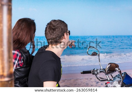 Close up Young Sweethearts on a Motorcycle Taking a Break at the Beach While Looking at the Beautiful Ocean. - stock photo