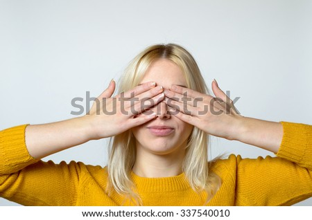 Close up Young Woman Covering her Eyes with Bare Hands Against Gray Background.