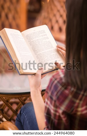 Close-up young woman is reading a book at a coffee shop. - stock photo