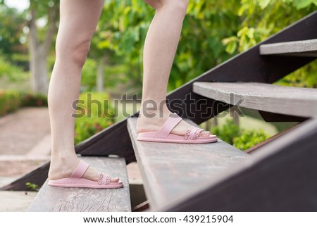 Close up young woman is walking up the steps wood.Close up young woman stepping up a staircase. - stock photo