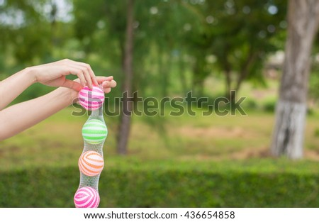 Close up young woman playing ball in the garden.Close up young woman playing colorful plastic balls for kid activity.