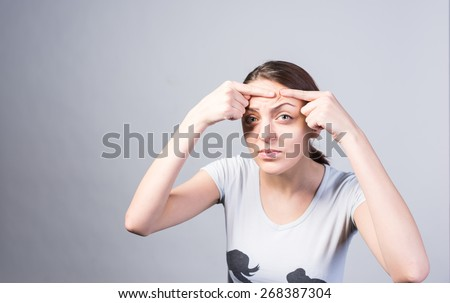 Close up Young Woman Pricking Pimple on her Forehead While Looking at the Camera Seriously. Captured in Studio with Gray Background - stock photo