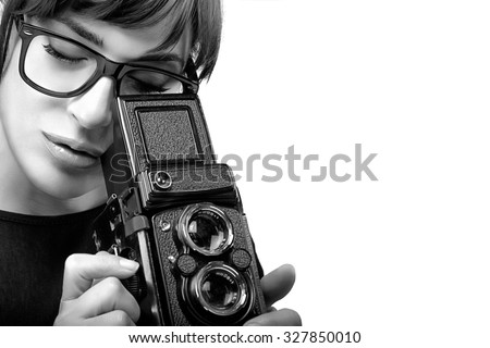 Close up Young Woman with Glasses Capturing Photo Using Vintage Camera. Monochrome Portrait Isolated on White Background with Copy Space at the Right - stock photo