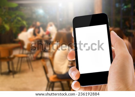 Close uphand holding phone with blank screen on coffee cafe background - stock photo
