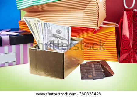 Close view ar colorful paper shopping bags and boxes with money and debit cards against green background - stock photo