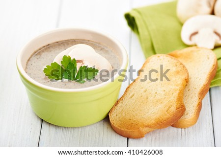 Close view at delicate cheese cream soup with mushrooms and crispy bread on a table