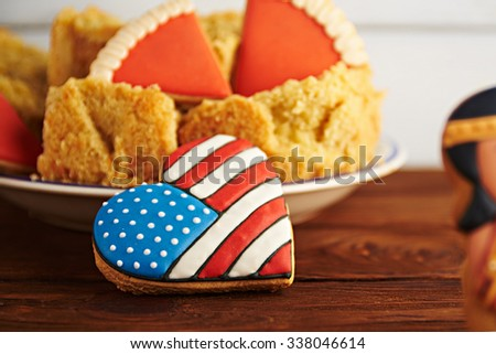 Close view at figures of gingerbread american flag in a heart shape with Thanksgiving pumpkin pie on a wooden background and part of cookie in blur. Shallow depth of field - stock photo