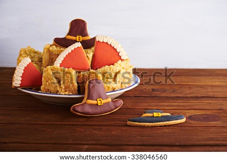 Close view at figures of gingerbread pilgrims hats with Thanksgiving pumpkin pie on a wooden background - stock photo