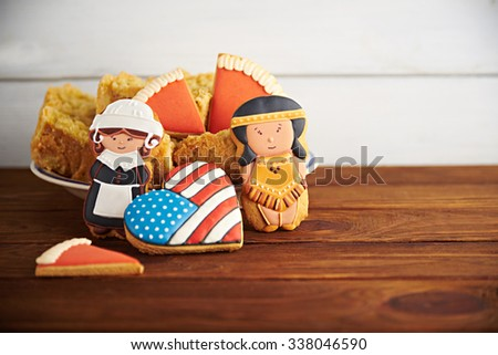 Close view at figures of gingerbread pilgrims, indians and american flag in a heart shape with Thanksgiving pumpkin pie on a wooden background - stock photo