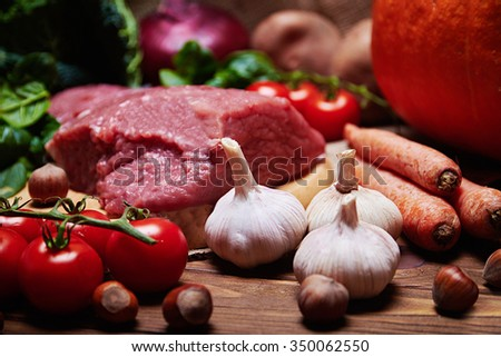 Close view at garlic with variety of fresh vegetables, raw meat, mushrooms and nuts on a burlap cloth and a wooden background - stock photo