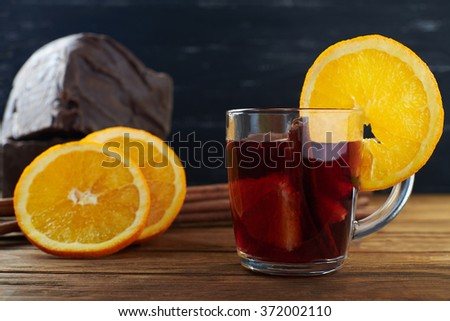 Close view at red mulled wine with fruits, cinnamon sticks with big piece of black chocolate on background on a wooden table  - stock photo
