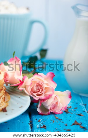 Close view at roses on a blue wooden background with cup of coffee and milk. Romantic mood. Scattered chocolate.