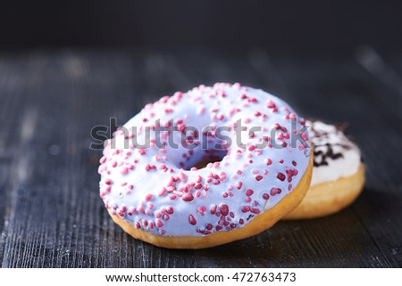 Close view at tasty donuts with blue and vanilla icing on a dark wooden background. Shallow depth of field