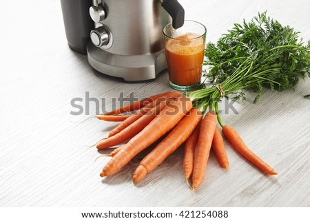 Close view metallic professional juicer with glass filled with tasty juice for breakfast from organic farm carrots lying on wooden table. Isolated on white background in cafe shop - stock photo