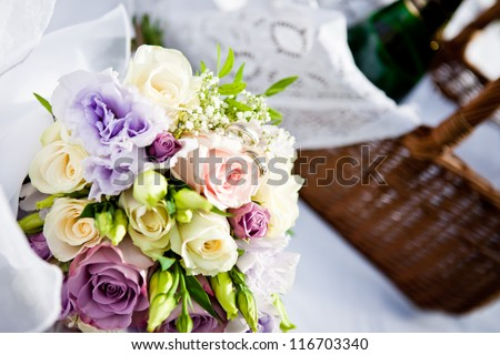Close view of a beautiful bouquet of flowers with rings and picnic basket