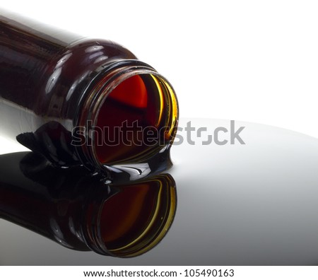 Close view of a bottle of molasses with the contents spilling onto a white background.