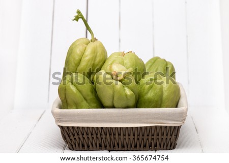 Close view of a chayote fruit on white wooden background. - stock photo
