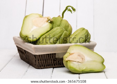 Close view of a chayote fruit on white wooden background.