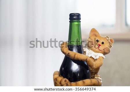 Close view of a cute cat doll on a green drink bottle - stock photo