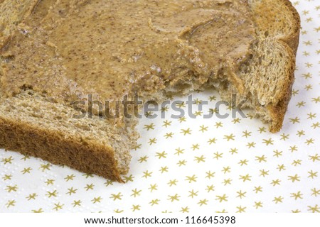 Close view of a piece of wheat toast with almond butter that has been bitten on a paper napkin. - stock photo