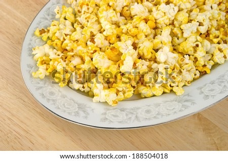 Close view of a platter filled with popcorn on a dining table. - stock photo