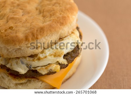 Close view of a sausage egg and cheese biscuit breakfast sandwich on a white plate upon a tan table cloth. - stock photo