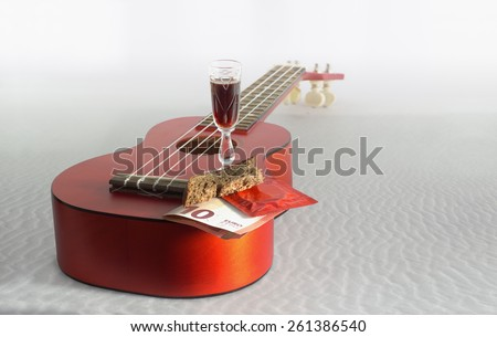Close view of a small guitar ukulele, a bread, ten euro banknote, a small glass with a drink and a condom at seaside â?? six simple things for a better life. - stock photo