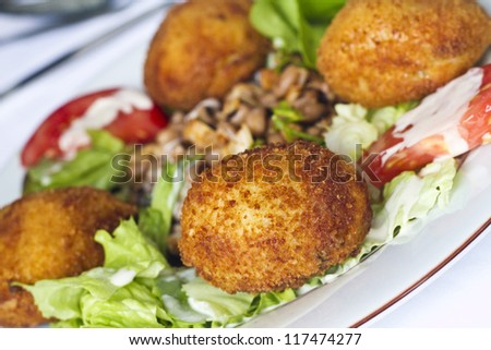 Close view of a tasty meal of chicken nuggets with salad.