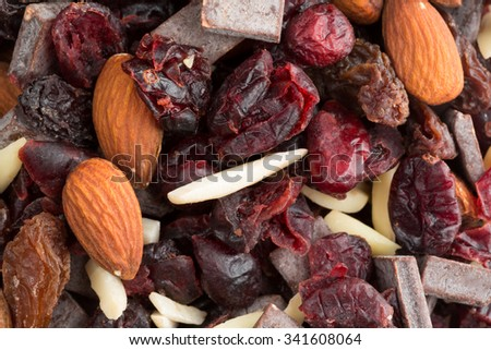 Close view of a trail mix consisting of dried cranberries, sliced almonds, raisins and chunks of chocolate illuminated with natural light. - stock photo