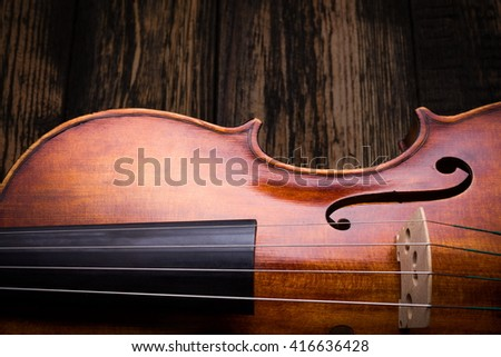 Close view of a violin strings and bout on dark wood - stock photo