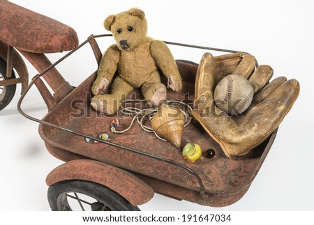 Close view of abandoned childhood toys Riding in a rusted red cart you find my old treasured toys  - stock photo