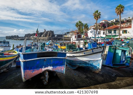 Close view of aged and abandoned fishing boats laying on the shore. Camara de Lobos marina, Madeira, Portugal.