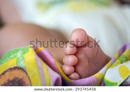 Close view of baby's foot on a colorful cloth - stock photo