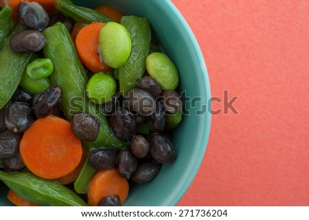 Close view of buttered carrots, black beans, edamame and snap peas in a bowl atop an orange background. - stock photo