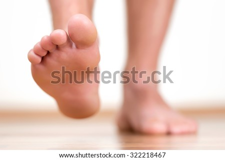 Close view of male feet making a step over home-like background.