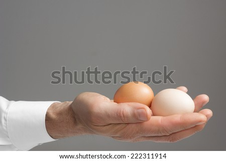 Close view of male's right hand with two hen's eggs./ Male's hand with hen's eggs.