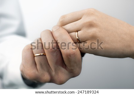 Close view of man's and woman's hands with wedding rings - stock photo