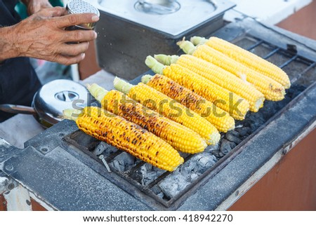 Close view of man's hands and sweet corn being prepared on grill on the open air - stock photo