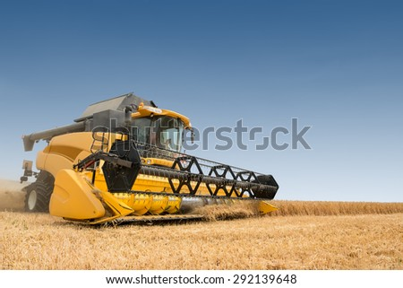 close view of modern combine harvester in action. - stock photo