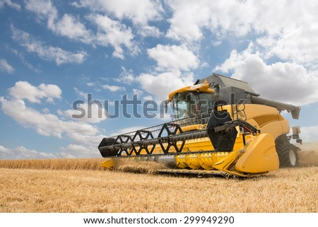 close view of modern combine harvester in action on cloudy blue sky background - stock photo