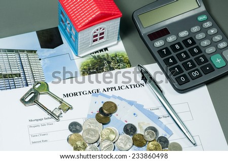 Close view of mortgage application form, house key, ballpoint pen, coins, money and calculator concept - stock photo