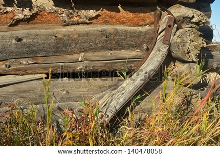 Close view of old abandoned log barn with an antique yoke leaning against the barn