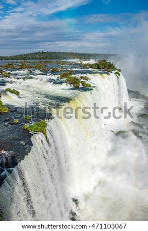Close view of one of the Cataratas water falls under blue sky and a lot of water mist in the air at the Foz do Iguassu park, Brazil.