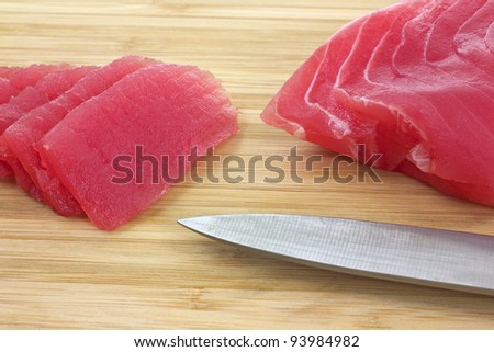 Close view of several pieces of yellowfin tuna sliced on wood cutting board with knife blade. - stock photo